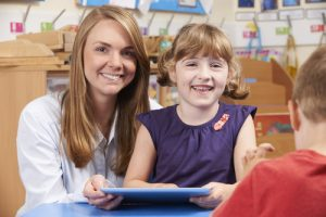 Teacher Helping Elementary Scool Pupil To Use Digital Tablet