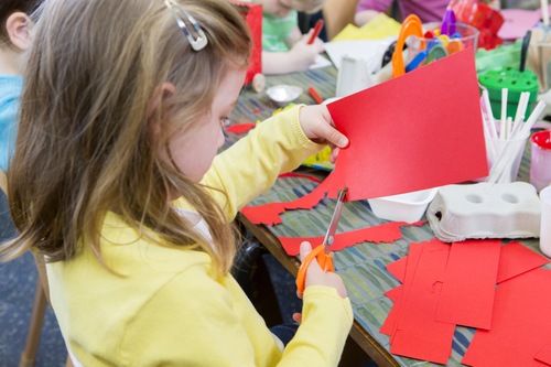 Little girl using scissors to cut shapes from a red piece of paper. she is in a nursery class with other students.