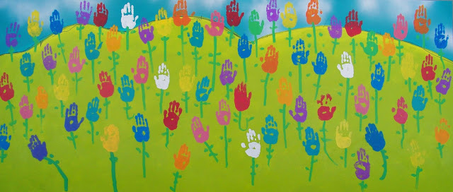 harmony day hand art of children on green hill